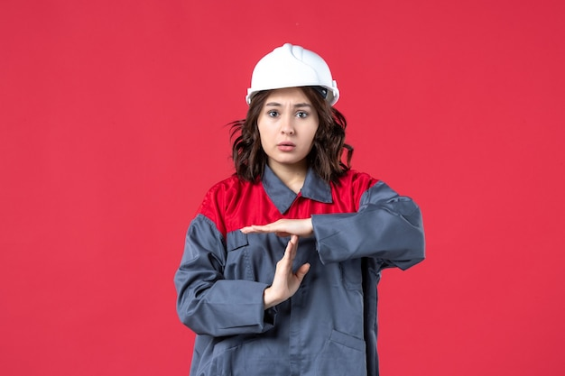 Vista dall'alto del costruttore femminile sconvolto in uniforme con elmetto e che fa un gesto di arresto su sfondo rosso isolato