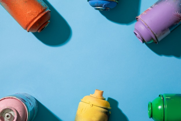 Top view of used spray paint cans on blue background with free space for text