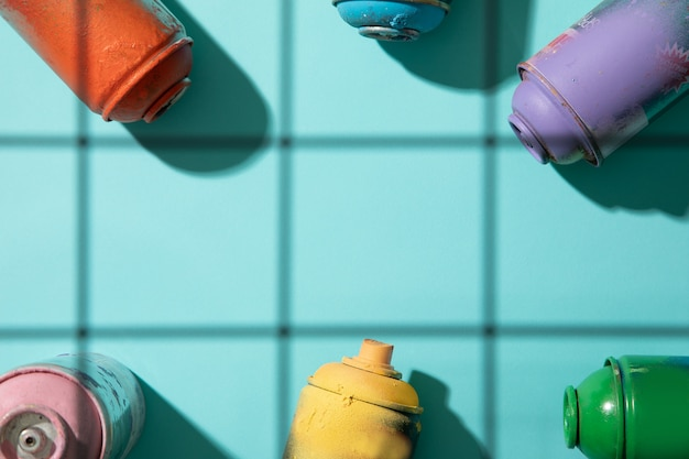 Top view of used spray paint cans on cyan background with grid shadows and free space for text