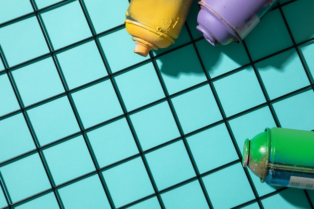 Top view of used spray paint cans on top of a metal grid, on cyan background with free space for text