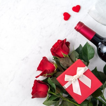 Top view of valentine day gift with rose and wine, festive design concept for special holiday dating meal.