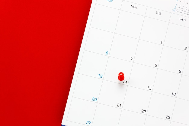 Top view valentine's day the red pin mark at calendar on red background.