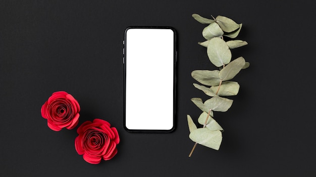 Top view of valentine's day roses with smartphone and plant