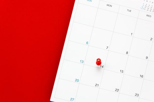Вид сверху день святого валентина красной значком pin в календаре на красном фоне.