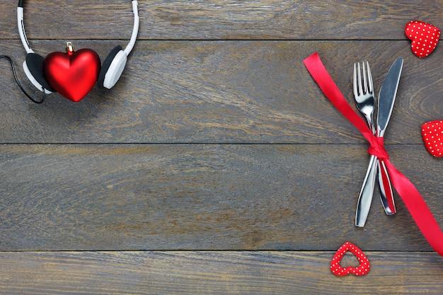 Вид сверху валентина день и музыка background.dinner набор и любовь музыка вилка ножа красная лента наушники и сердце формы на деревянные с копией пространства.