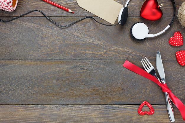 トップビューのバレンタインデーと音楽background.dinnerセットと愛の音楽フォークナイフ赤いリボンヘッドフォンとハートの形の木製のコピースペース。