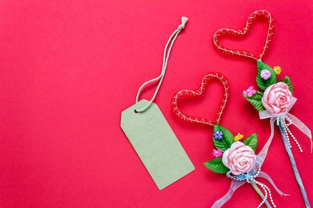 Вид сверху валентина день фон и decorations.love форма букет подарок и поздравительная открытка на красном фоне с копией пространства.