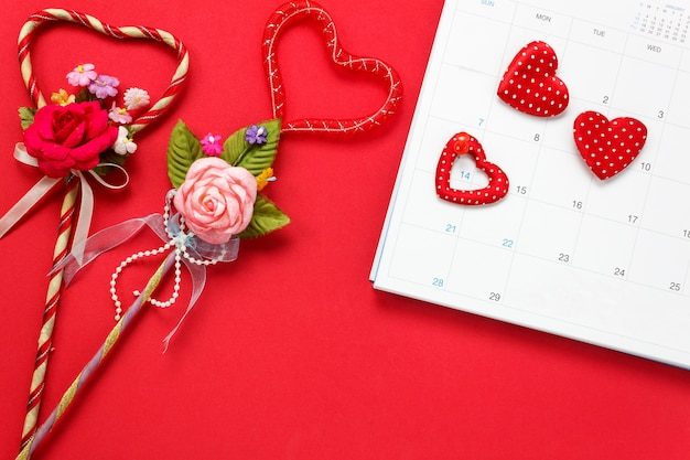 Top view valentines day background and decorations.the red pin mark february 14 at calendar and love shape  bouquet gift on red background and heart  shape with copy space.