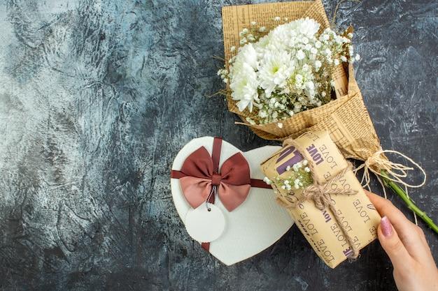 Вид сверху концепция дня святого валентина цветы подарочная коробка в форме сердца в женской руке на темном фоне с местом для копирования