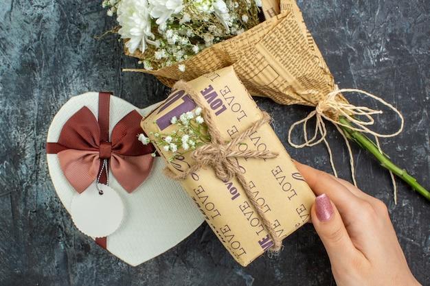 Вид сверху день святого валентина концепция цветы коробка в форме сердца подарок в женской руке на темном фоне