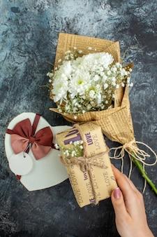Вид сверху день святого валентина концепция цветы в форме сердца коробка подарок в руке женщины на темном фоне