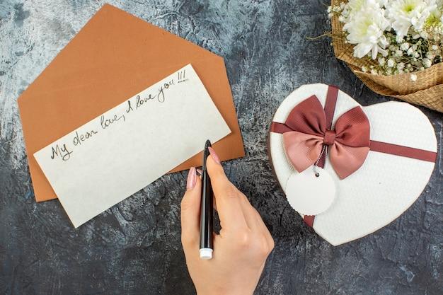 Вид сверху день святого валентина концепция цветы в форме сердца коробка подарок любовное письмо ручка в женской руке на темном фоне