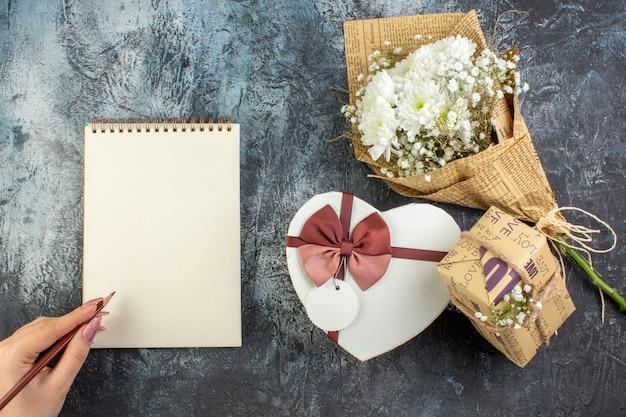 Вид сверху день святого валентина концепция цветы в форме сердца коробка подарочная тетрадь карандаш в женской руке на темном фоне