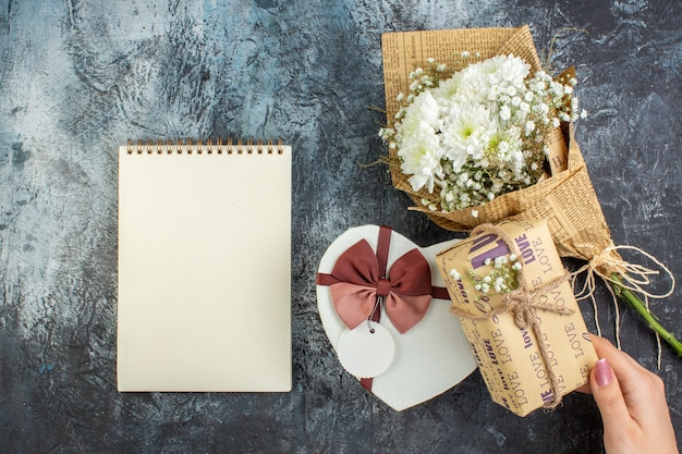Вид сверху день святого валентина концепция цветы в форме сердца коробка ноутбук подарок в женской руке на темном фоне