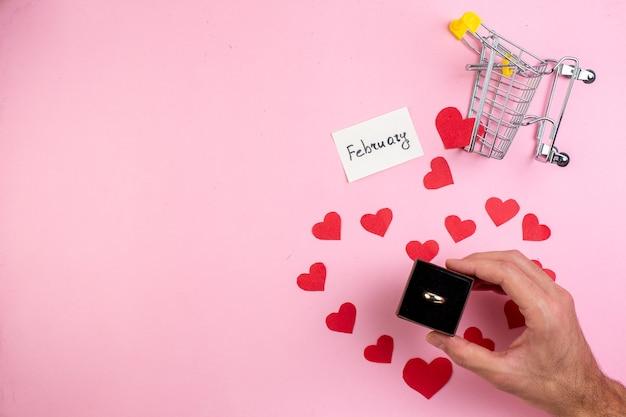 Вид сверху концепция дня святого валентина наклейки с красным сердцем мини-тележка обручальное кольцо в мужской руке на синем столе с местом для копирования