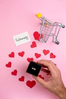 Вид сверху концепция дня святого валентина наклейки с красным сердцем мини-тележка обручальное кольцо в мужской руке на синем столе