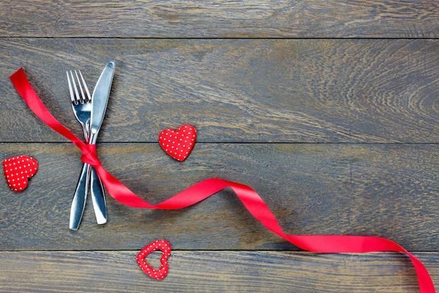 Вид сверху valentines day.dinner set fork and knife, красная лента и форма сердца на дереве с копией пространства.