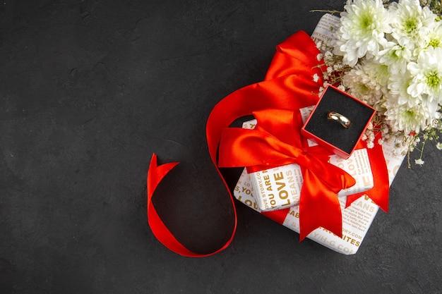 Вид сверху подарок на день святого валентина цветы кольцо в коробке на темном фоне с местом для копирования