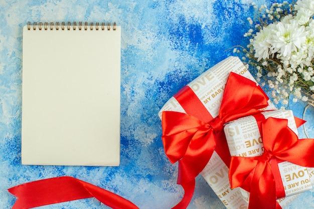 Вид сверху день святого валентина подарки ноутбук цветы на синем фоне