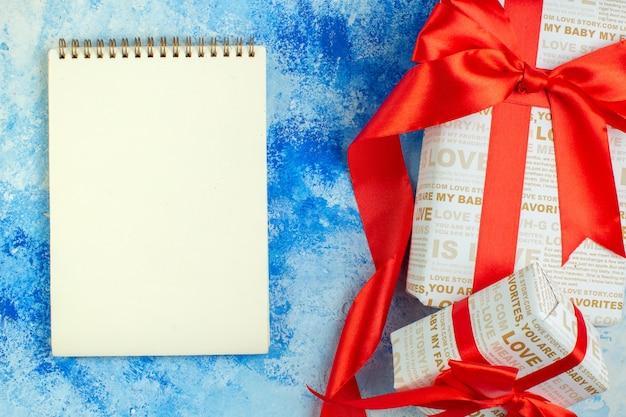 Вид сверху подарки на день святого валентина с блокнотом с красными лентами на синем фоне