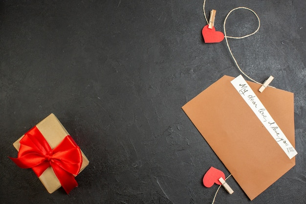 Вид сверху записка на день святого валентина с подарком на темном фоне любовник любовь пара брак цвет сердца чувство