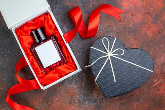 Вид сверху на день святого валентина настоящий аромат на темной поверхности подарок духи любовь чувство цвет пара счастье женщина