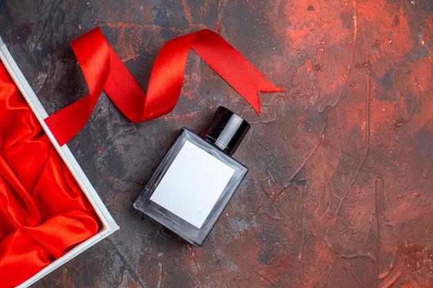 Vista dall'alto profumo di san valentino regalo con confezione su superficie scura coppia regalo profumo sensazione colore