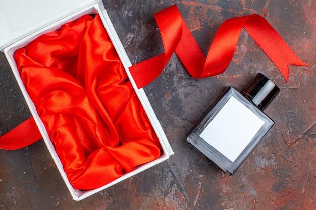 Vista dall'alto profumo regalo di san valentino con pacchetto su una superficie scura regalo di coppia profumo amore sensazione colore matrimonio donna