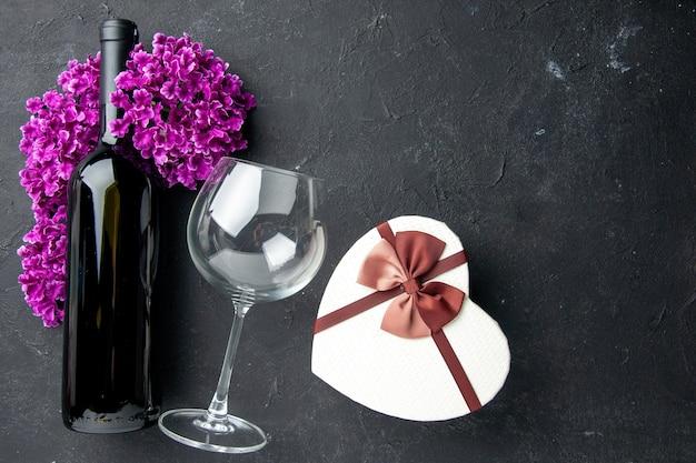Вид сверху подарок на день святого валентина с цветами и бутылкой вина на темном фоне чувство любви пара подарок цвет алкоголь брак