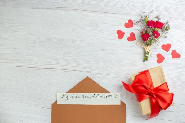 Вид сверху день святого валентина подарок с запиской на белом фоне любовь праздник страсть любовник пара брак сердце чувство записка