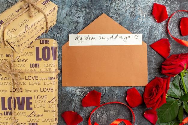 Вид сверху день святого валентина подарок с красными розами и записка на сером фоне пара брак любовь праздник чувство сердце страсть