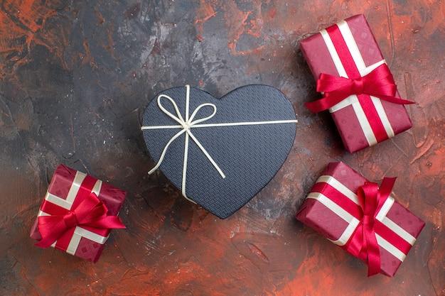 Подарки на день святого валентина сверху в красной упаковке на темной поверхности