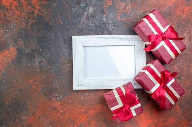 상위 뷰 발렌타인 데이는 어두운 표면에 그림 프레임이 있는 선물을 제공합니다. 사진 애호가 색상 선물 사랑을 느끼는 당신을 사랑합니다