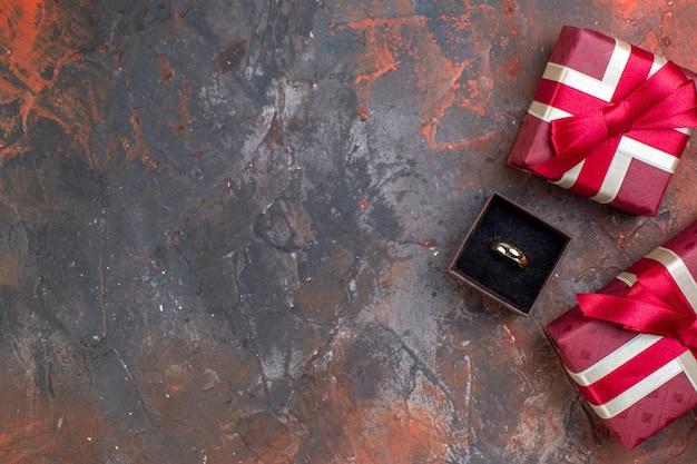 Vista dall'alto regali di san valentino con anello su sfondo scuro regalo profumo amore sentimento colore coppia donna anello matrimonio