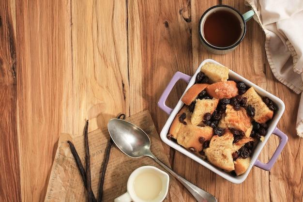 상위 뷰 바닐라 계피 건포도 빵과 버터 푸딩은 텍스트 복사 공간이 있는 정사각형 베이킹 접시에 있습니다. 나무 테이블에.