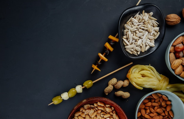 Top view of varied beer snacks sunflower seeds peanuts almond pickled olives and string cheese on black with copy space