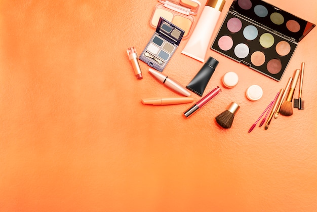 Top view of varied cosmetics and makeup tools on orange background with copyspace