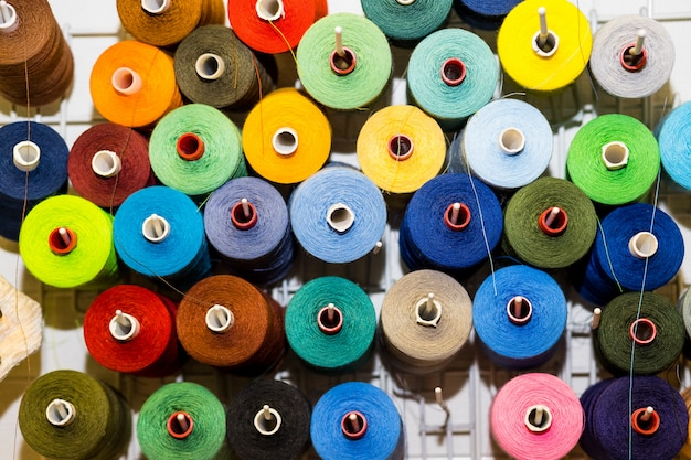 Top view variety big and used spools of colorful sewing threads. tailor shop theme background, textiles and clothing industry concept. selective focus, space for text