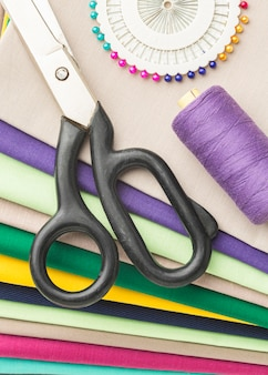 Top view of variety of fabrics with scissors and needles