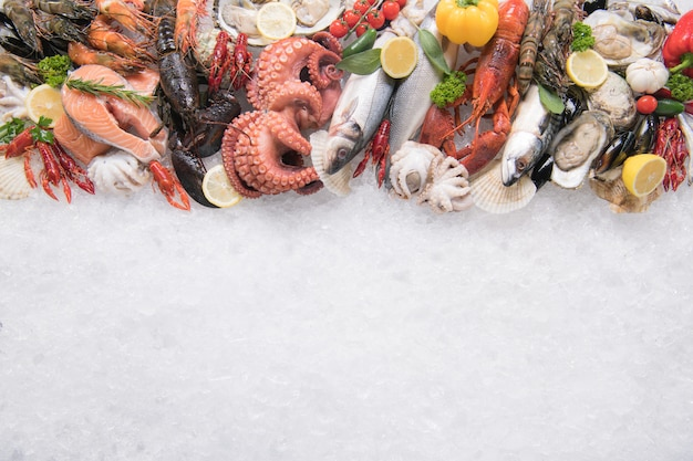 Top view of variety of fresh fish and seafood on ice with copy-apace