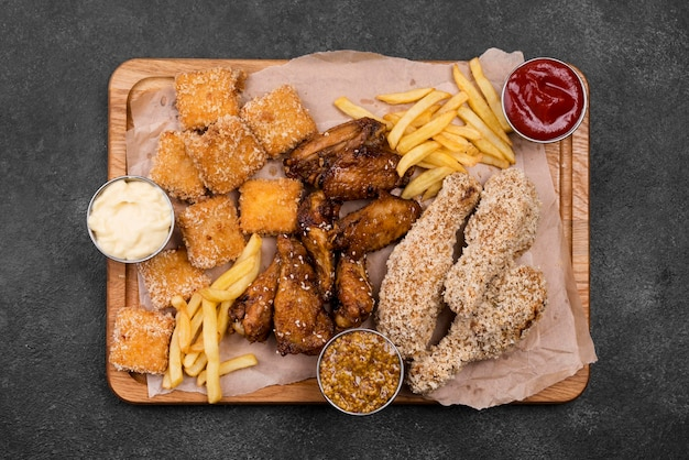 Top view of variety of fried chicken with sauces and french fries