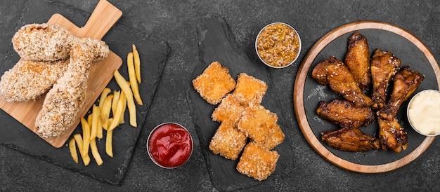 Vista dall'alto di varietà di pollo fritto con salse e patatine fritte
