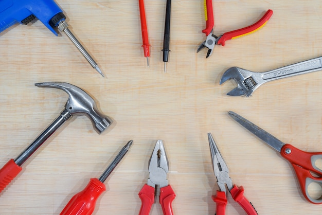Top view of variety handy tools on wooden board background for labor day.