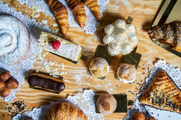Top view of a variety of homemade cakes such as tarts, lemon pie, lionesses, mochi, croissant, eclair, sweet and delicious.