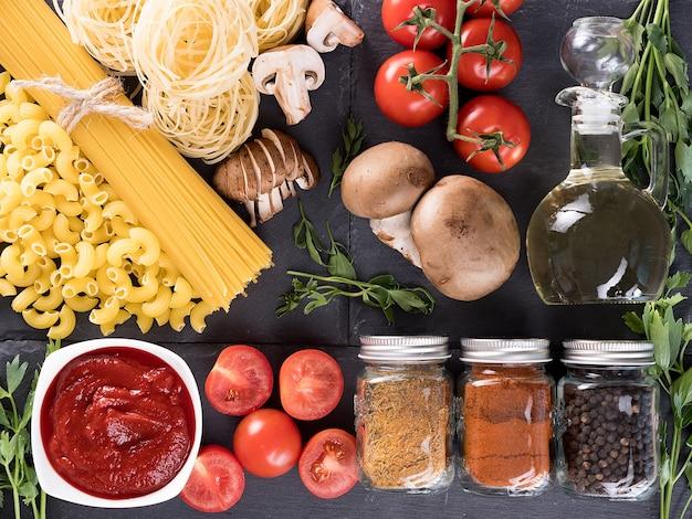 トマトソース、フレッシュトマト、マッシュルーム、緑、さまざまなスパイス、ひまわり油の入ったボトルの横にあるさまざまな生の生パスタの上面図