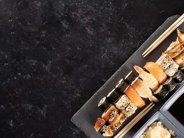 暗い石の背景に寿司のトップビューの様々な。アジア料理。健康的な食事