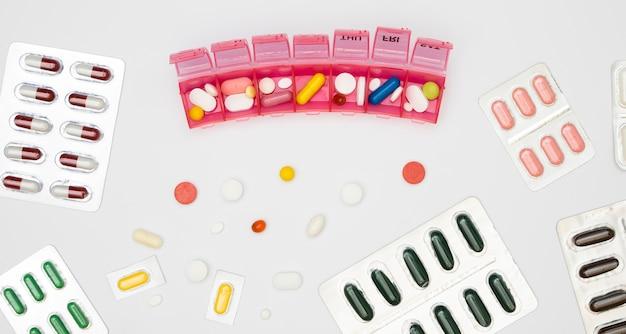 Vista dall'alto della varietà di pillole in fogli e contenitore con giorni settimanali