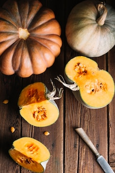 Top view variety of pumpkins on wooden background and knife
