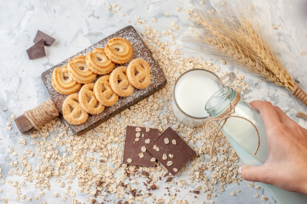 Top view various biscuits on chopping board chocolates wheat spikes hand pouring milk to glass scattered oats on grey background