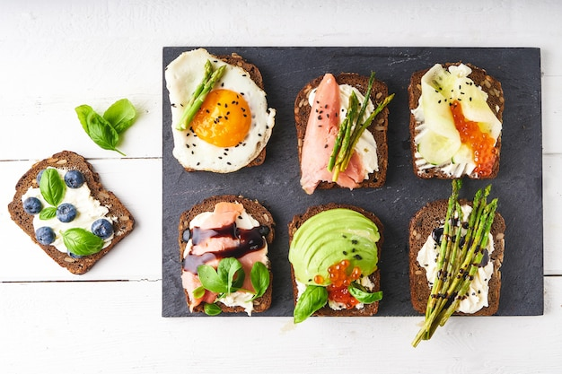Top view of various bruschettas,sandwiches with different healthy fillihgs served on dark plate